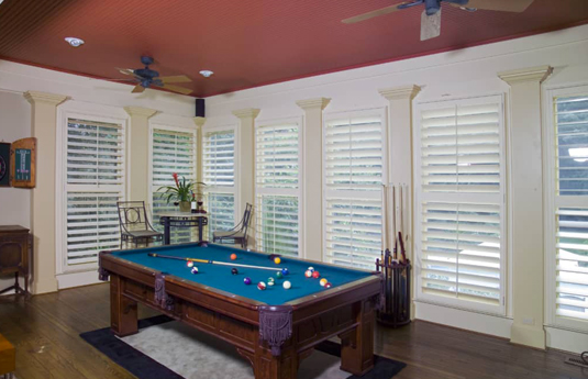 pool table in a room with plantation shutters